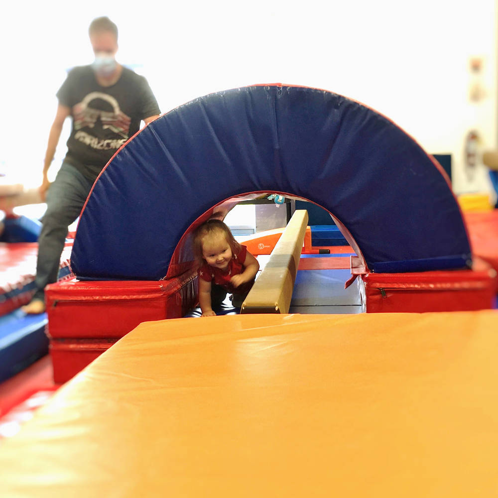 Coach looks on as young gymnast on a balance beam practices a back walkover at Gymworld Adventures in Gymnastics facility in North London.